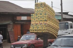 Un hombre transportando varios colchones