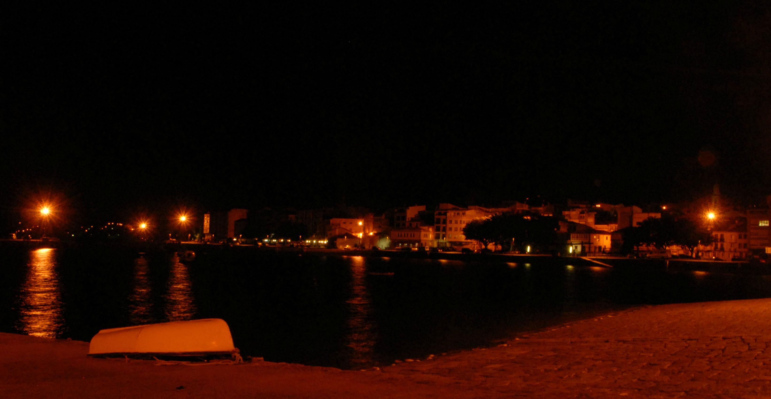 Vista nocturna do porto e  casco histórico da vila, no que destaca a Igrexa de Santa Comba