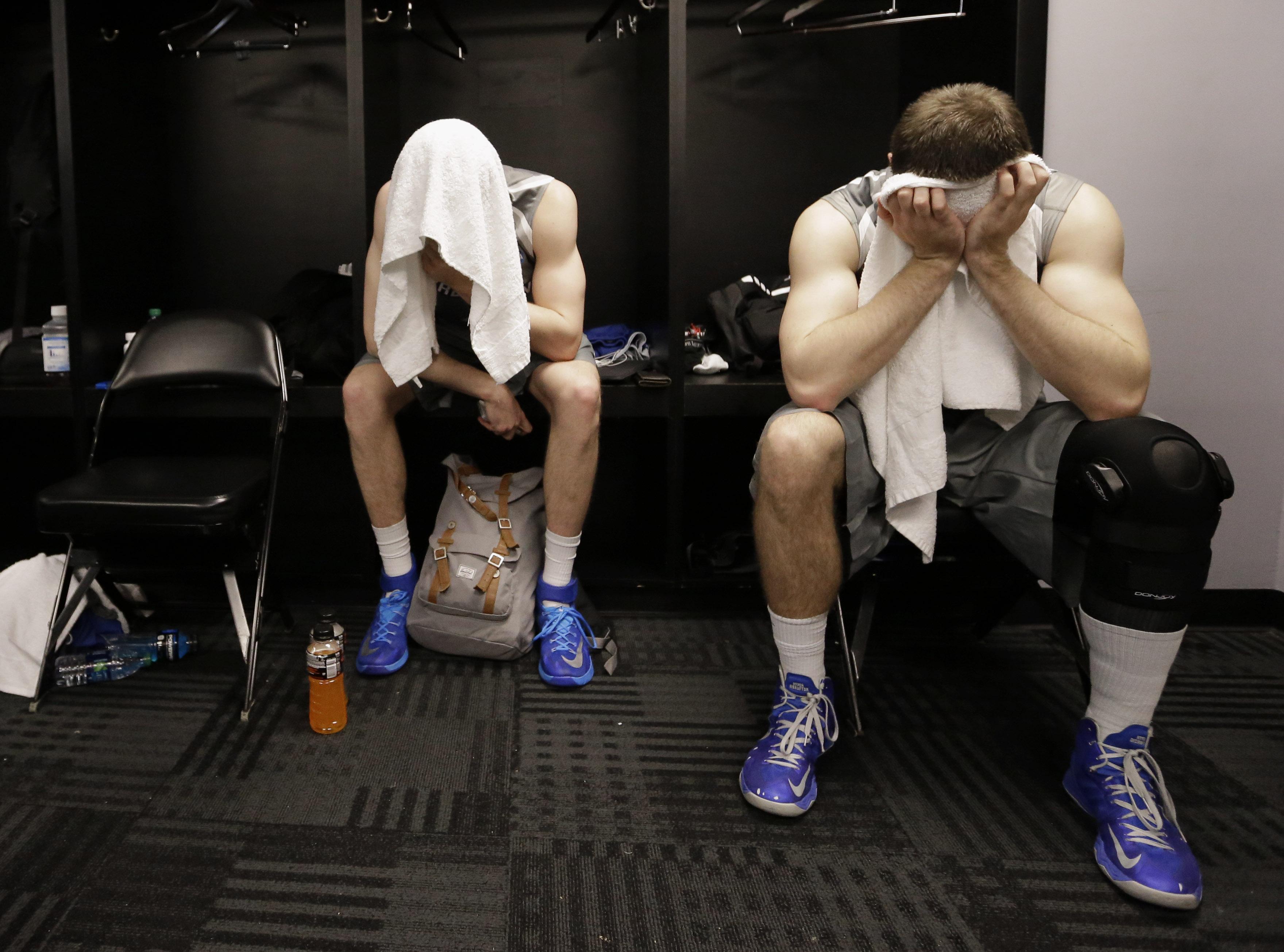 Alex Olsen y Ethan Wragge ocultan su frustración tras la tela de sus toallas. | © David J. Phillip, AP Photo.